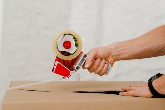 Ritaglia le mani sulla scatola di imballaggio Foto Gratuite