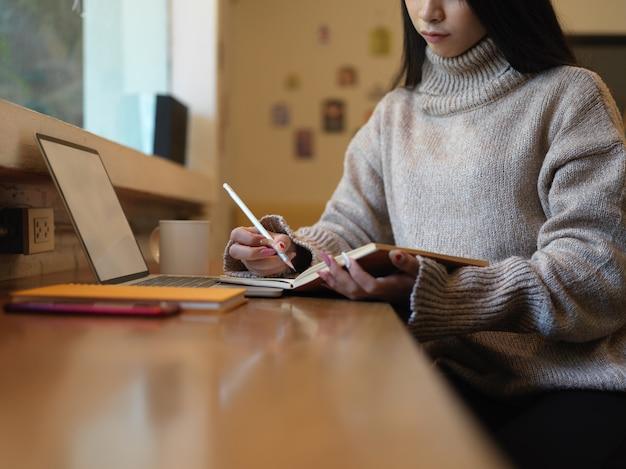 Ritagliata colpo di donna prendendo nota mentre si lavora con mock up laptop sul bancone della caffetteria Foto Premium
