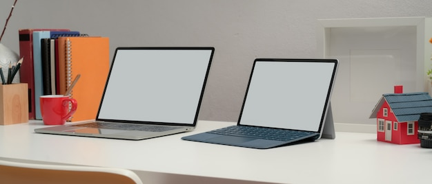 Ritagliata colpo di due laptop con schermo vuoto sulla scrivania in ufficio con libri e decorazioni nella stanza del ministero degli interni Foto Premium
