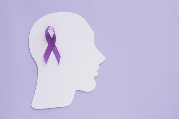 Ritaglio di carta cerebrale con nastro viola su sfondo viola, consapevolezza di epilessia e alzheimer, disturbo convulsivo, concetto di salute mentale Foto Premium