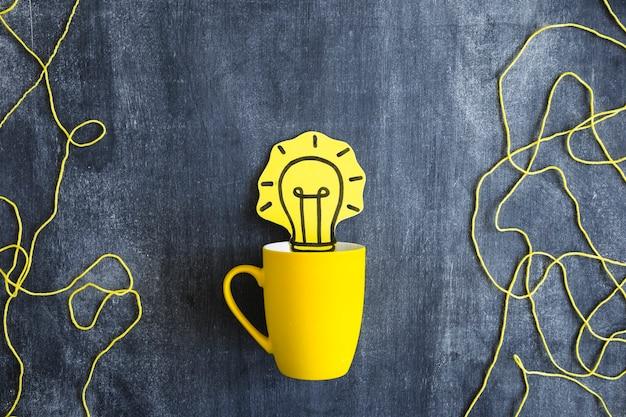 Ritaglio di carta della lampadina gialla nella tazza con la corda della lana sulla lavagna Foto Gratuite