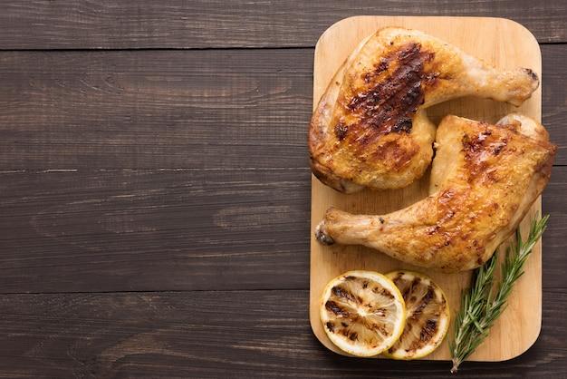 Ritardo e rosmarini arrostiti del pollo su fondo di legno Foto Premium
