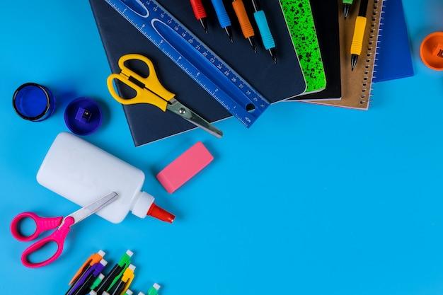 Ritorno a scuola, materiale scolastico su sfondo azzurro Foto Premium