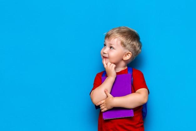 Ritorno a scuola ritratto di felice bambino sorpreso sul blu Foto Premium