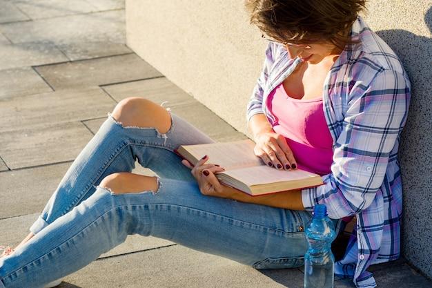 Ritratto all'aperto del libro di lettura della donna Foto Premium