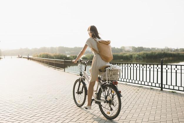 Ritratto all'aperto di giovane castana attraente in un cappello su una bicicletta. Foto Gratuite
