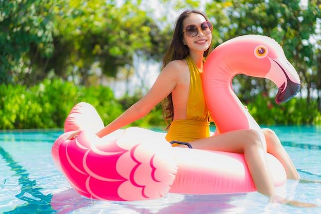 Ritratto bella giovane donna asiatica sul galleggiante gonfiabile del fenicottero nella piscina alla località di soggiorno dell'hotel Foto Gratuite