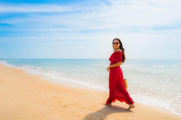 Ritratto bella giovane donna asiatica sulla spiaggia e sul mare Foto Gratuite
