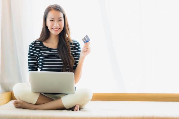 Ritratto bella giovane donna asiatica utilizzando computer notebook o laptop con carta di credito per lo shopping Foto Gratuite
