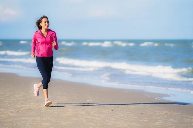 Ritratto bello giovane funzionamento asiatico della donna o esercizio sul paesaggio della natura del tropica della spiaggia Foto Gratuite