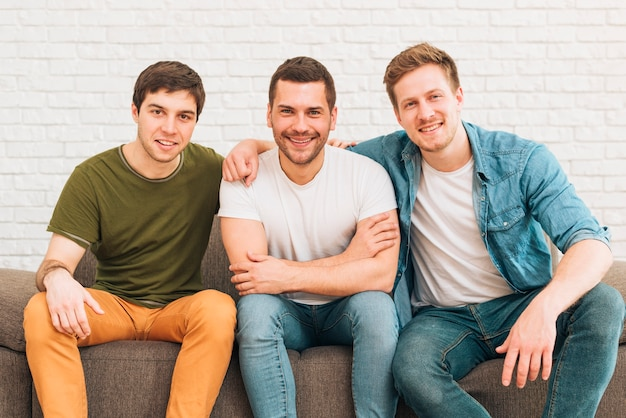 Ritratto degli amici maschii sorridenti che si siedono insieme sul sofà Foto Gratuite