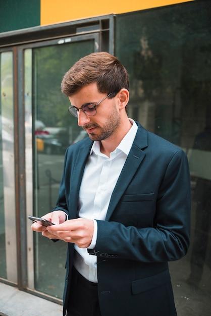 Ritratto degli occhiali d'uso di un uomo d'affari facendo uso del telefono cellulare Foto Gratuite