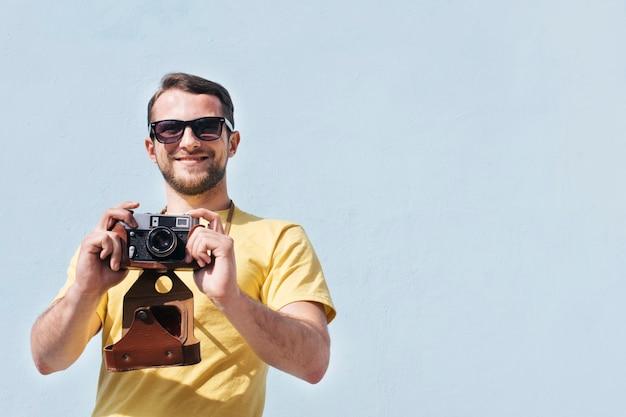 Ritratto degli occhiali da sole da portare sorridenti dell'uomo che catturano maschera con la retro macchina fotografica Foto Gratuite