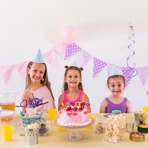 Ritratto dei bambini sorridenti che indossano il cappello del partito che celebra la festa di compleanno Foto Gratuite