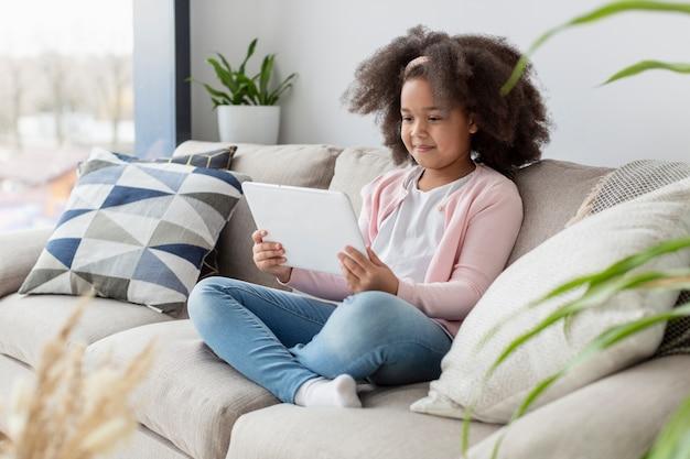 Ritratto dei cartoni animati di sorveglianza della ragazza sul sofà Foto Gratuite