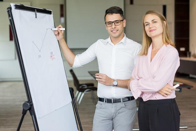 Ritratto dei colleghi sorridenti di affari che disegnano piano sul grafico di vibrazione. Foto Gratuite