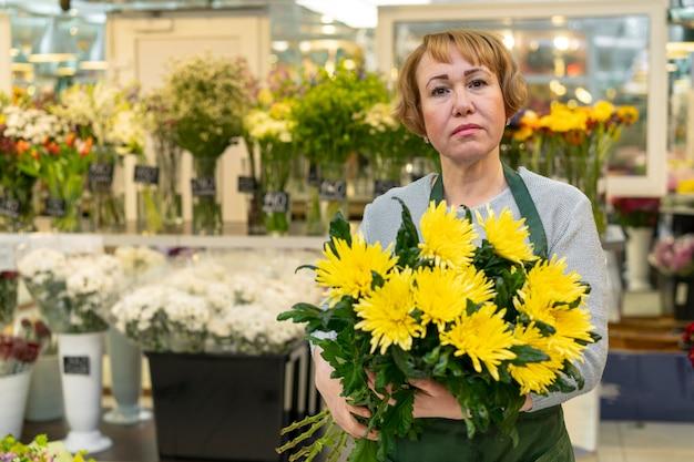 Ritratto dei fiori senior della tenuta della donna Foto Gratuite