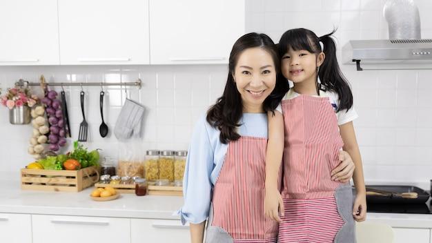 Ritratto dei grembiuli d'uso della famiglia asiatica nella cucina Foto Premium