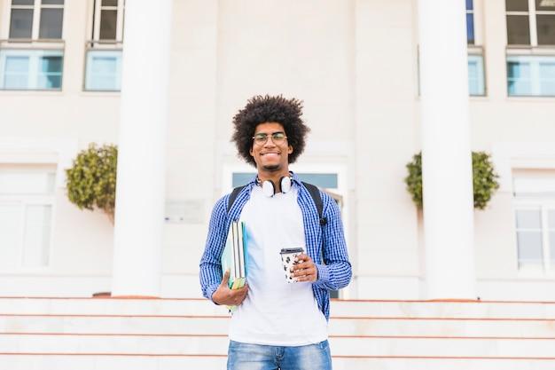 Ritratto dei libri adolescenti felici della tenuta dello studente maschio di afro e tazza di caffè asportabile che stanno davanti all'istituto universitario Foto Gratuite
