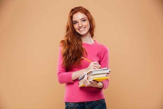 Ritratto dei libri felici felici di una tenuta della ragazza della testarossa Foto Gratuite