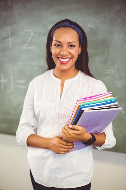 Ritratto dei libri sorridenti della tenuta del maestro di scuola in aula Foto Premium