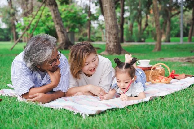 Ritratto dei nonni e della nipote asiatici che mettono sul campo di vetro verde all'aperto, famiglia che gode insieme del picnic nel concetto di giorno di estate Foto Premium