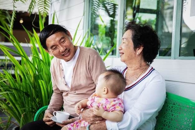 Ritratto dei nonni e della nipote asiatici sorridenti felici del bambino a casa Foto Premium