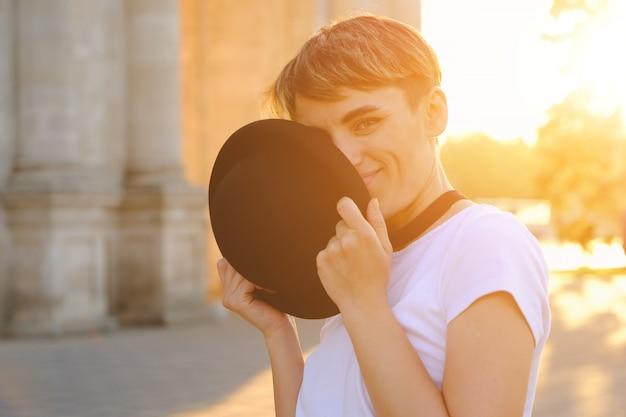 Ritratto dei pantaloni a vita bassa femminili con trucco naturale e breve taglio di capelli che godono del tempo libero all'aperto Foto Gratuite