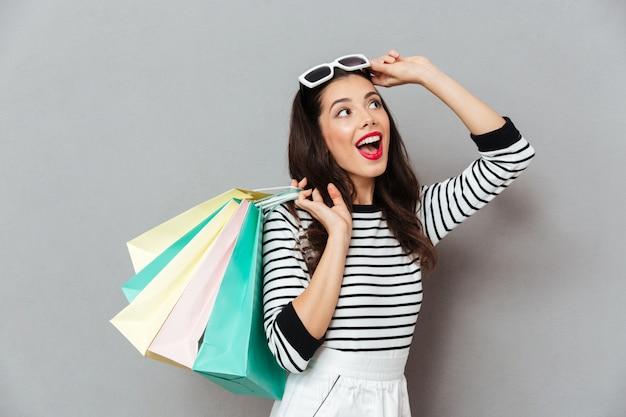 Ritratto dei sacchetti della spesa allegri di una tenuta della donna Foto Gratuite