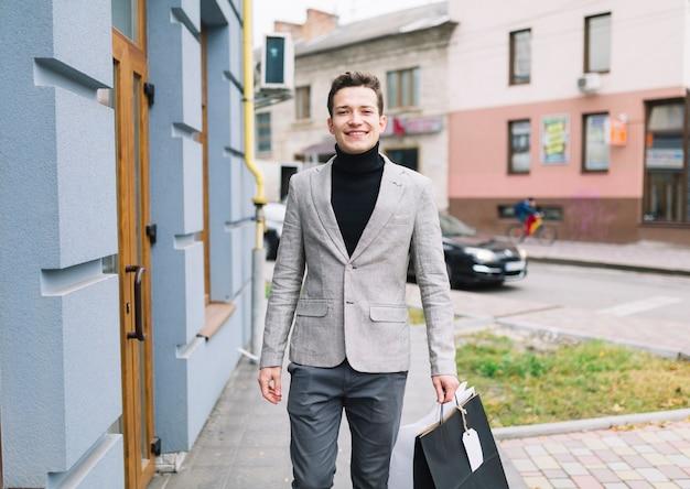 Ritratto dei sacchetti della spesa sorridenti della tenuta del giovane che camminano sulla via Foto Gratuite