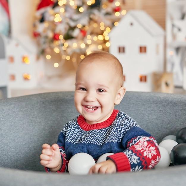 Ritratto del bambino del bambino con l'albero di natale. natale carino bambino. concetto di vacanza in famiglia. sala giochi per bambini. natale nella stanza dei bambini. Foto Premium