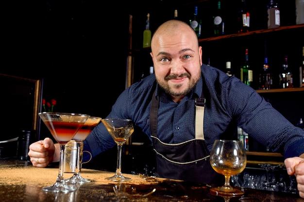 Ritratto del barista arrabbiato e stressato con la cravatta a farfalla dietro la barra con le bevande alcoliche intorno. stile di vita stressante del concetto di barista Foto Premium