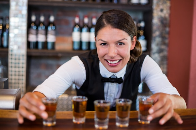 Ritratto del barista che posiziona i bicchierini sul contatore della barra Foto Premium