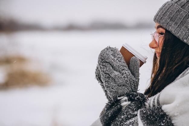 Ritratto del caffè bevente della giovane donna in un parco di inverno Foto Gratuite