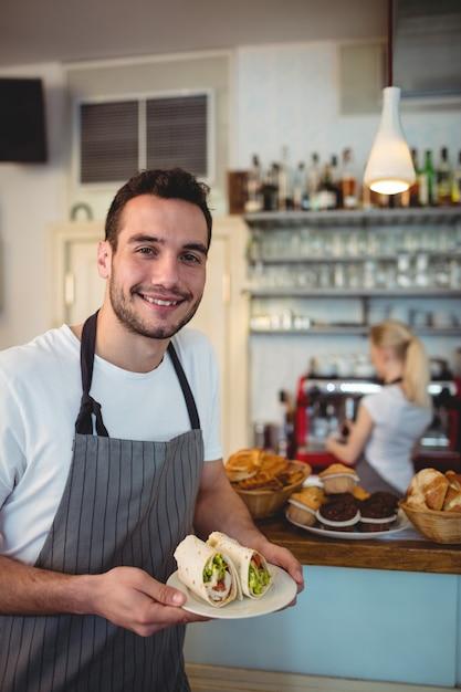 Ritratto del cameriere felice con i panini freschi al caffè Foto Premium