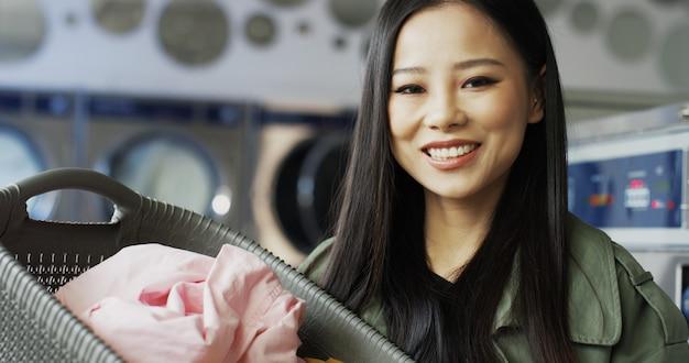 Ritratto del canestro grazioso asiatico della tenuta della giovane donna con i vestiti puliti dopo il lavaggio e sorridere alla macchina fotografica. chiuda in su di bella ragazza alla moda con il sorriso nella stanza di servizio di lavanderia. Foto Premium