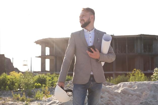 Ritratto del cellulare sorridente della tenuta dell'uomo dell'architetto e casco con il modello al cantiere Foto Gratuite