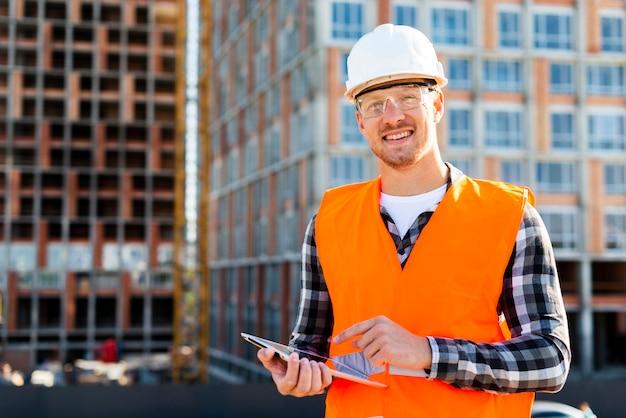 Ritratto del colpo medio di ingegnere sorridente che esamina macchina fotografica Foto Gratuite