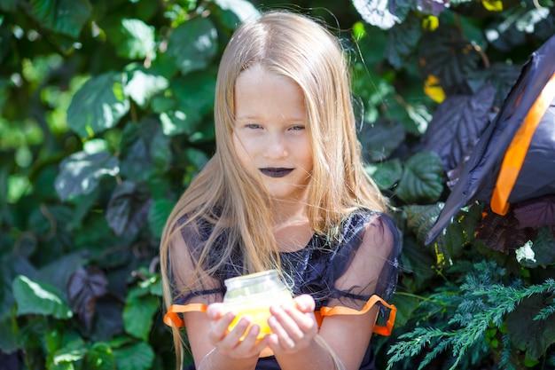 Ritratto del costume da portare della strega della bambina felice con la scopa su halloween Foto Premium