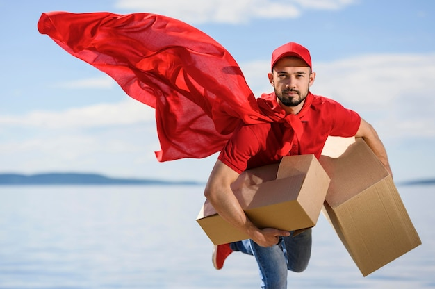 Ritratto del fattorino che indossa il mantello da supereroe Foto Gratuite