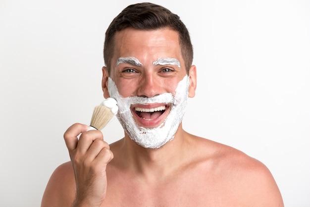Ritratto del giovane felice che applica schiuma da barba contro il fondo bianco Foto Gratuite