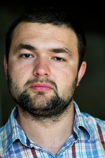 Ritratto del giovane fotogenico moderno intelligente sicuro sicuro barbuto con taglio di capelli corto e gli occhi neri gentili che guardano meditatamente a porte chiuse su gray Foto Premium