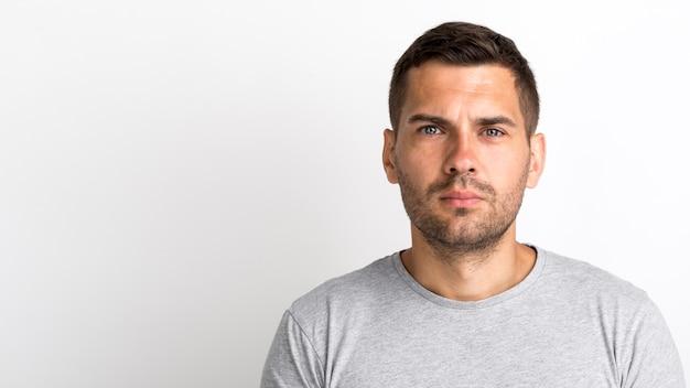Ritratto del giovane in maglietta grigia che esamina macchina fotografica che sta contro la parete bianca Foto Gratuite