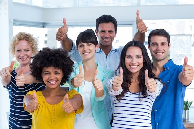 Ritratto del gruppo creativo che gesturing i pollici su Foto Premium