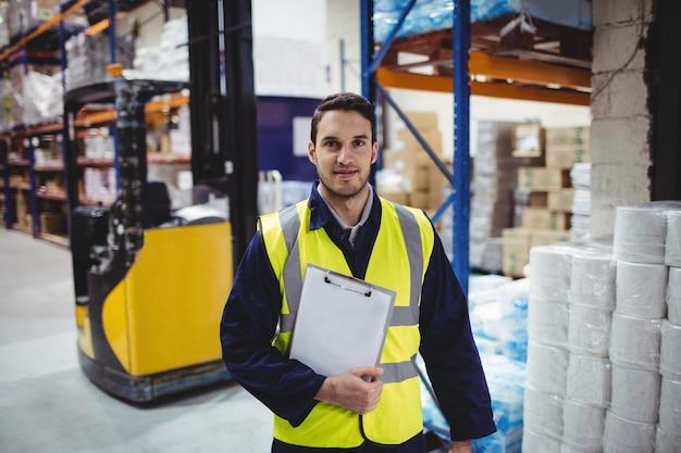 Ritratto del lavoratore del magazzino con la lavagna per appunti in magazzino Foto Premium