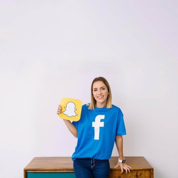 Ritratto del logo sorridente dello snapchat della tenuta della giovane donna Foto Gratuite