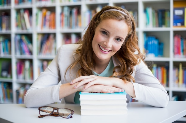 Ritratto del maestro di scuola sorridente con i libri in biblioteca Foto Premium