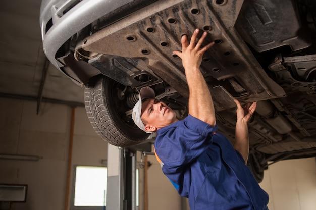 Ritratto del meccanico di automobile che lavora con gli strumenti sotto l'automobile Foto Premium