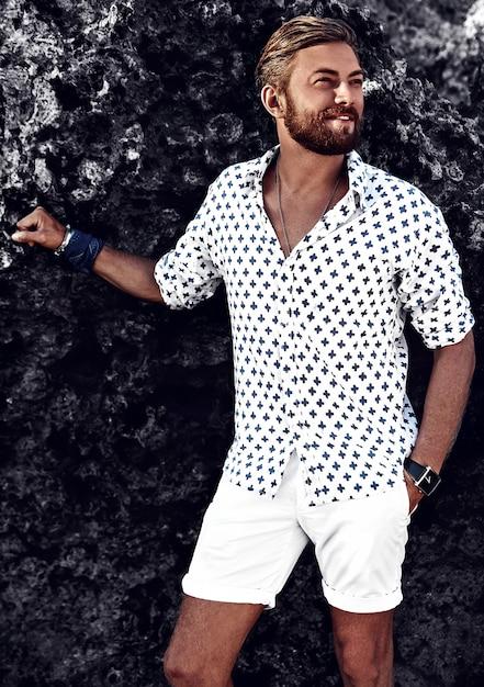 Ritratto del modello bello dell'uomo di modo che indossa i vestiti bianchi che posano vicino alle rocce sulla spiaggia Foto Gratuite