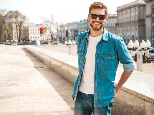 Ritratto del modello dell'uomo d'affari lumbersexual sorridente alla moda bello dei pantaloni a vita bassa. uomo vestito con abiti giacca di jeans. Foto Gratuite